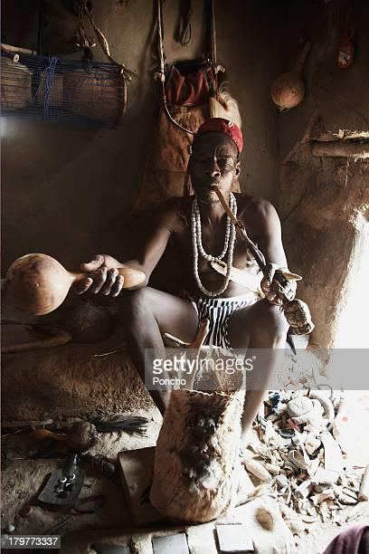Medicine man sitting in a mud hut