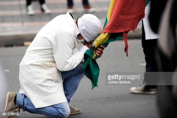 TOPSHOT A medicine student kneels holding a Bolivian national flag amid a protest against a new law that penalizes medical malpractice near the...