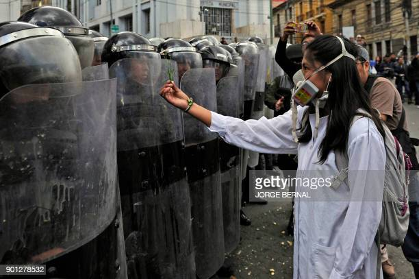 A medicine student offers a flower to a police officer in riot gear during a protest against a new law that penalizes medical malpractice near the...
