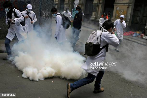 Medicine students clash with riot police officers during a protest against President Morales new law that proposes penal sanctions to medical...