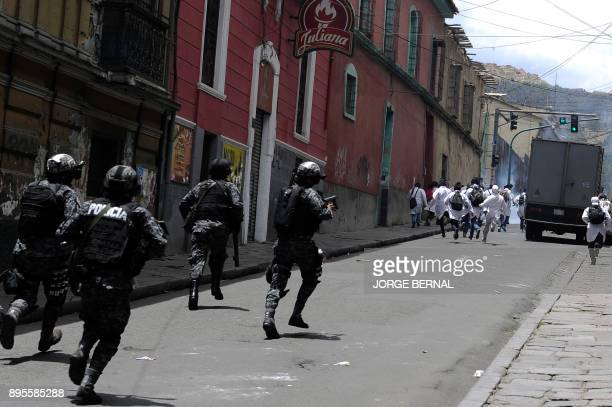 Medicine students escape from riot police during clashes within a protest against President Morales' new law which proposes penal sanctions for...