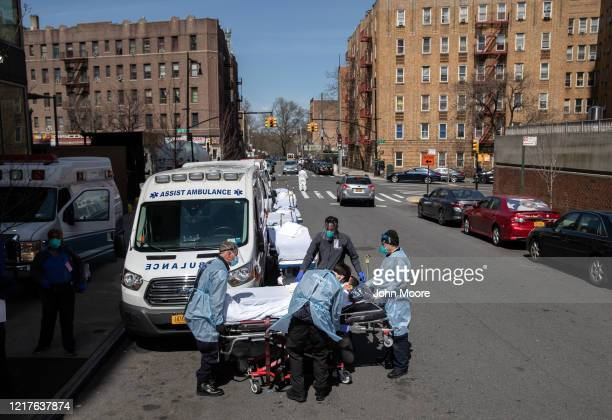 Medics and hospital workers prepare to lift a COVID-19 patient onto a hospital stretcher outside the Montefiore Medical Center Moses Campus on April...