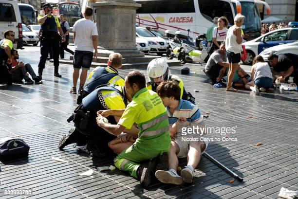 Medics and police tend to injured people near the scene of a terrorist attack in the Las Ramblas area on August 17, 2017 in Barcelona, Spain....