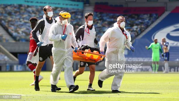 Medics and stretcher bearers wearing PPE enter the field to attend to Arsenal's German goalkeeper Bernd Leno during the English Premier League...