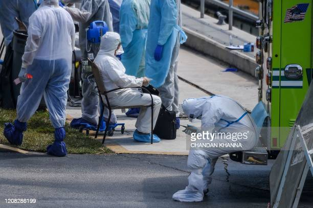 Medics assist a sick crew member from one of two boats which requested assistance as they arrive at the US Coast Guard Base in Miami on March 26 2020...
