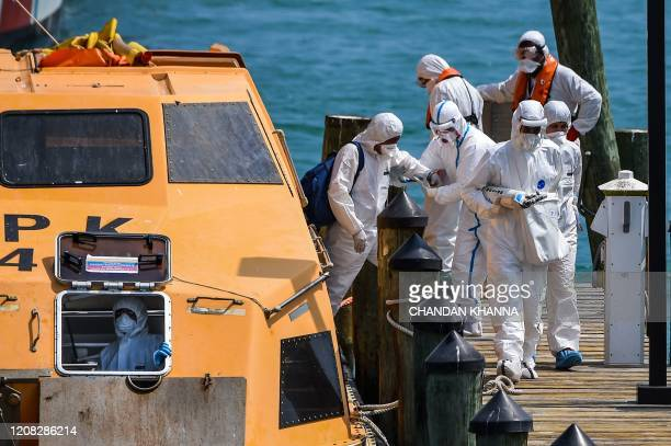 Medics assist a sick crew members of two lifeboats as they arrive at the US Coast Guard Base in Miami on March 26 2020 The US Coast Guard is...