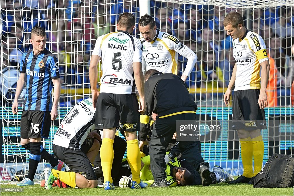 Medics attend to goalkeeper Boubacar Barry of Sporting Lokeren OVL as he lies injured after banging his head on the goal post as he leapt to make a save during the Jupiler Pro League play-off 1 match between Club Brugge and Sporting Lokeren on May 5, 2013 in Brugge, Belgium.