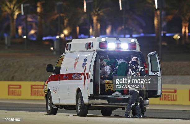 Medics attend to Haas F1's French driver Romain Grosjean after a crash at the start of the Bahrain Formula One Grand Prix at the Bahrain...