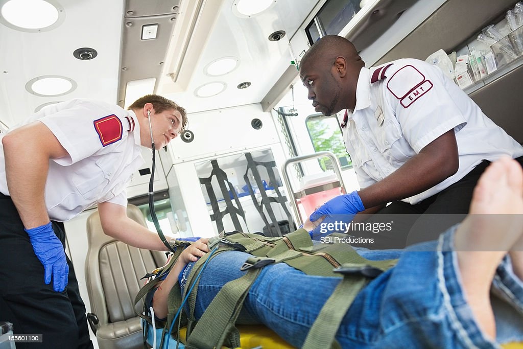 Medics caring for and working on patient in ambulance : Stock Photo
