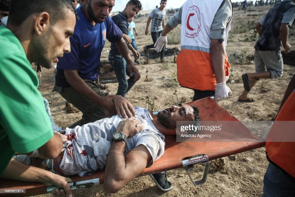 Medics carry a wounded Palestinian as Israeli forces intervene to disperse Palestinians taking part in the 'Great March of Return' demonstration near Israel-Gaza border at Al-Bureyc refugee camp in Gaza City, Gaza on July 20, 2018.