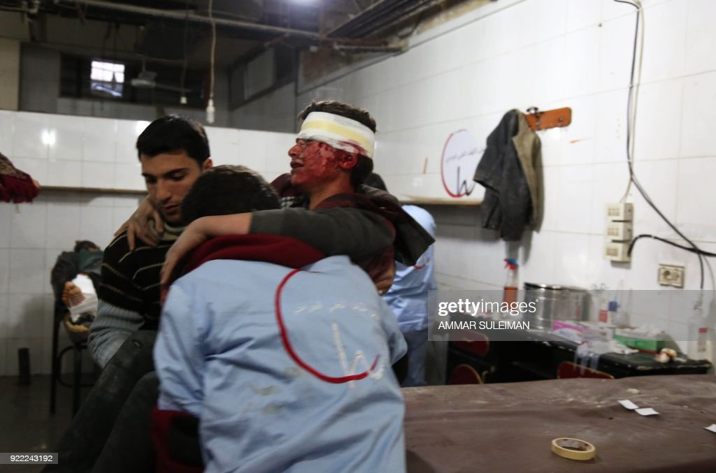 Medics carry a wounded Syrian youth at a make-shift hospital in Kafr Batna following Syrian government bombardments on the besieged Eastern Ghouta region on the outskirts of the capital Damascus on February 21, 2018. Syrian jets carried out more deadly raids on Eastern Ghouta as Western powers and aid agencies voiced alarm over the mounting death toll and spiralling humanitarian catastrophe. PHOTO / Ammar SULEIMAN