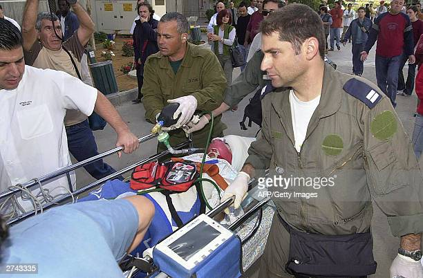 Medics carry an injured tourist woman into Beersheba hospital 19 November 2003 after she was shot at Rabin terminal in the border crossing between...