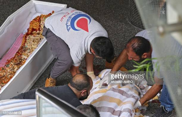 Medics carry the body of a 61-year-old man, who committed suicide due to the country's deepening economic downturn, into a coffin in the capital...