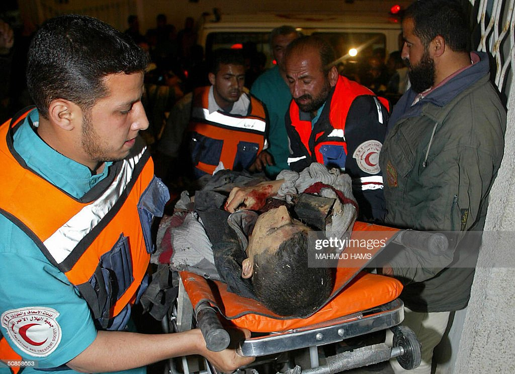Medics carry the body of a Palestinian i