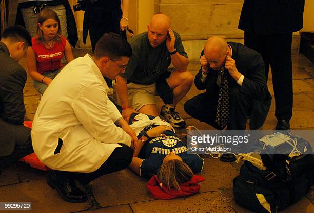 Medics check the vital signs of a student who fainted while on a tour in the Crypt of the Capitol