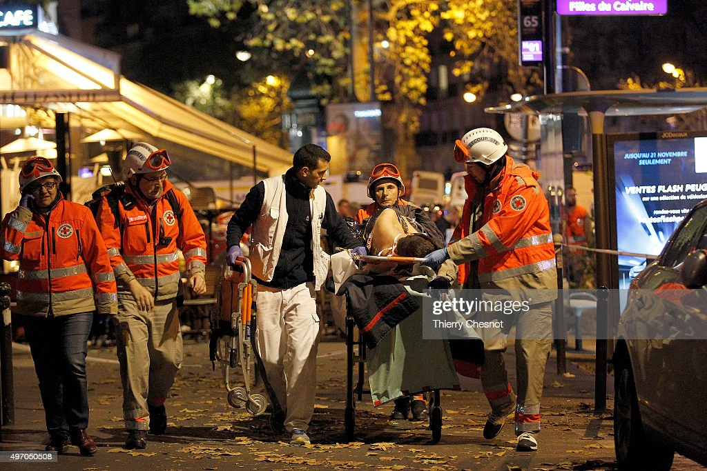 Medics evacuate an injured person on Boulevard des Filles du Calvaire, close to the Bataclan theater, early on November 14, 2015 in Paris, France. According to reports, over 150 people were killed in a series of bombings and shootings across Paris, including at a soccer game at the Stade de France and a concert at the Bataclan theater.