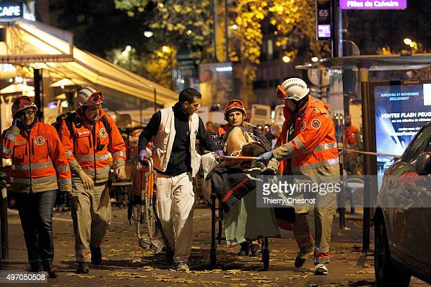Medics evacuate an injured person on Boulevard des Filles du Calvaire, close to the Bataclan theater, early on November 14, 2015 in Paris, France....
