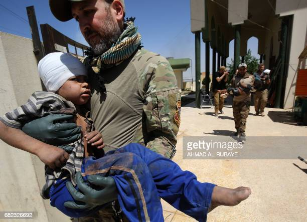 Medics from a US group providing emergency care from a mobile clinic help Iraqis to treat wounded displaced children on May 12 2017 during a...