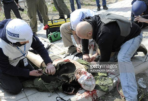 Medics from the Organization for Security and Cooperation in Europe mission give a first medical aid to Russian journalist Andrei Lunev after he was...