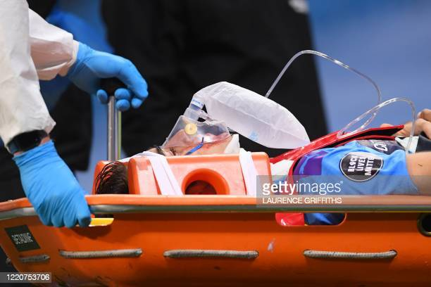 Medics in full PPE carry Manchester City's Spanish defender Eric Garcia off the pitch injured during the English Premier League football match...