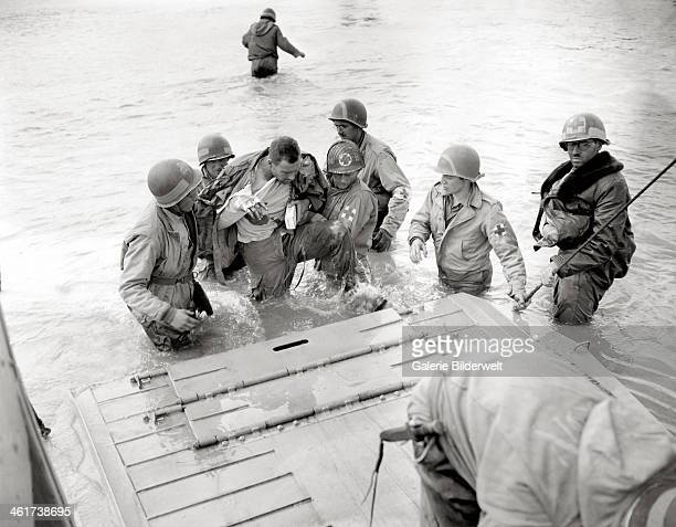 Medics of the 2nd Naval Beach Battalion help an injured paratrooper to board a Landing Craft Vehicle Personnel Some medics wear a red cross on a...