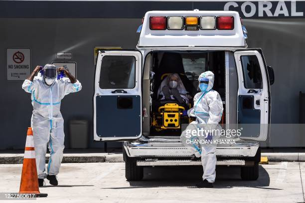 Medics prepares to transfer a patient on a stretcher from an ambulance outside of Emergency at Coral Gables Hospital where Coronavirus patients are...