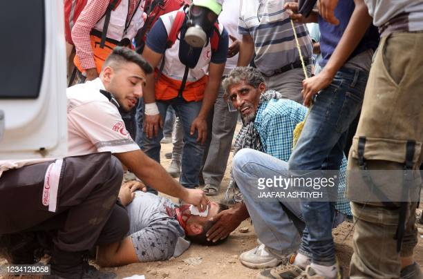 Medics provide first aid to an injured Palestinian protester amid clashes with Israeli security forces during a demonstration in the town of Beita...