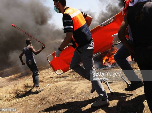 Medics rush in as Palestinians clash with Israeli soldiers at the border fence with Israel as mass demonstrations at the fence continue on May 14...