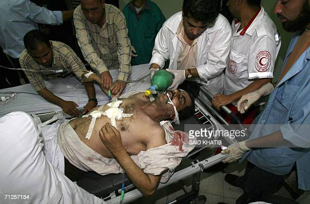 Medics rush with Palestinian Zakaria alBarbaraoui in the Naser hospital in the southern Gaza Strip town of Khan Yunis 21 June 2006 following an...