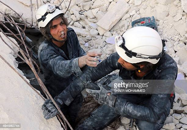 Medics search for survivors under the rubble following a reported air strike on the rebelheld neighbourhood of alKalasa in the northern Syrian city...