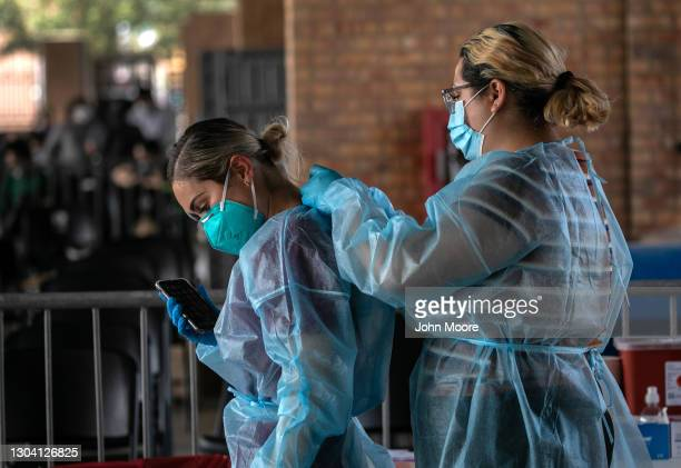 Medics suit up in PPE before testing asylum seekers for COVID-19 who had been released by the U.S. Border Patrol on February 25, 2021 in Brownsville,...