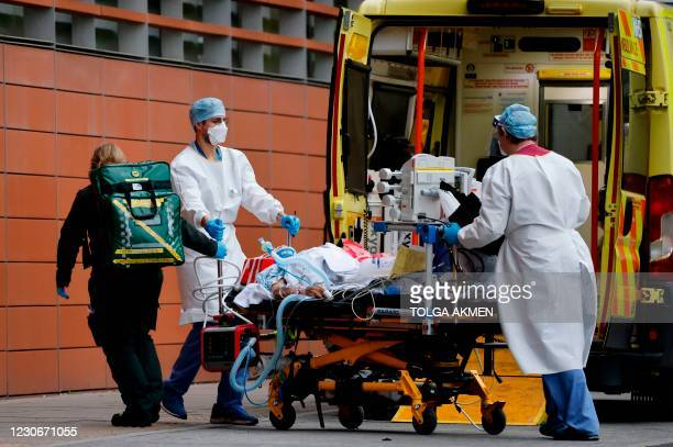 Medics take a patient from an ambulance into the Royal London hospital in London on January 19, 2021. - An estimated 12 percent of people in England...