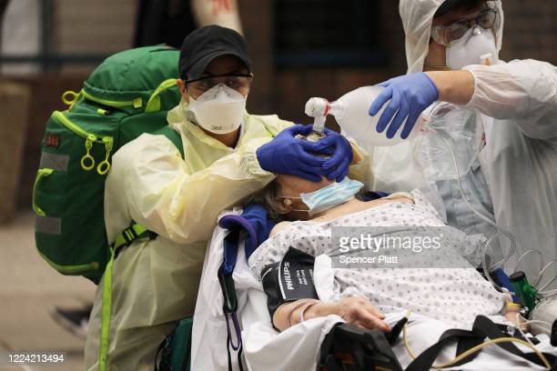 Medics take a patient in severe respiratory distress to an ambulance from a group home next to Maimonides Medical Center on May 11 2020 in the...