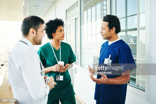 dokters praten terwijl het hebben van een pauze op het werk - koffiepauze stockfoto's en -beelden