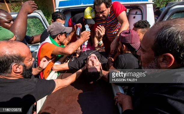 TOPSHOT Medics tend and provide blood to an Iraqi protester who was injured at a demonstration outside the southern port of Umm Qasr on November 5...