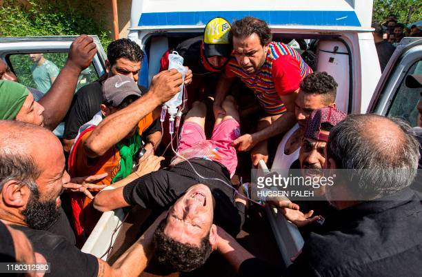 Medics tend and provide blood to an Iraqi protester who was injured at a demonstration outside the southern port of Umm Qasr on November 5 after...