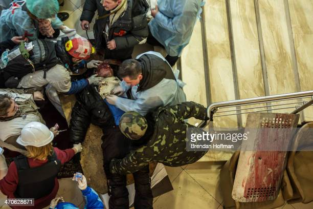 Medics tend to a gravely wounded antigovernment protester in the lobby of the Hotel Ukraine which has been converted to a medical clinic and...
