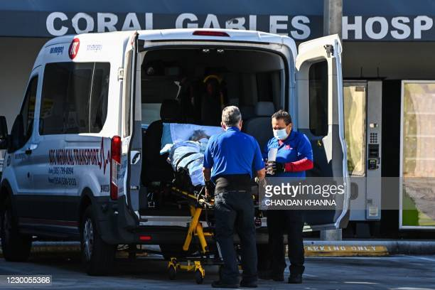 Medics transfer a patient on a stretcher from an ambulance outside of Emergency at Coral Gables Hospital where Coronavirus patients are treated in...