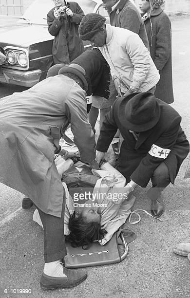 Medics treat the unconscious body of Civil Rights activist Amelia Boynton on a stretcher near the Edmund Pettus Bridge during the first Selma to...