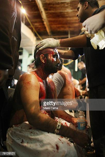 Medics treat wounded Shi'ite Muslims after they flagellated themselves during a procession marking the festival of Ashura outside the alKhoei Islamic...