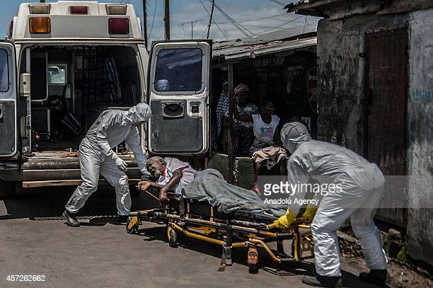 Medics wear protective gear carry a Liberian patient 70yearold Francis Koneh suspected of being infected with the Ebola virus during his transfer to...