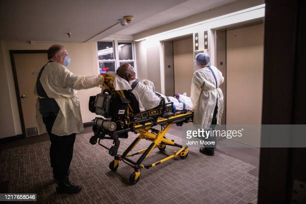 Medics wearing personal protection equipment , transport an African American patient showing COVID-19 symptoms from his apartment on April 04, 2020...