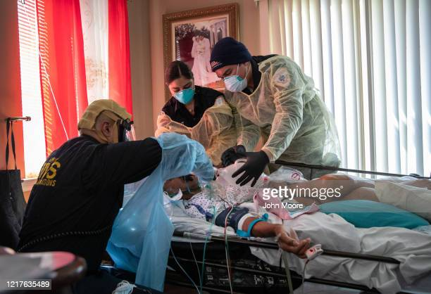 Medics wearing personal protective equipment intubate a gravely ill patient with COVID19 symptoms at his home on April 06 2020 in Yonkers New York...
