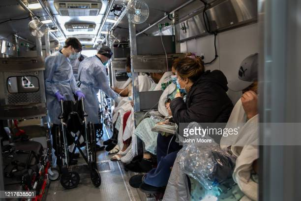 Medics wearing personal protective equipment , unload COVID-19 patients arriving to the Montefiore Medical Center Moses Campus on April 07, 2020 in...