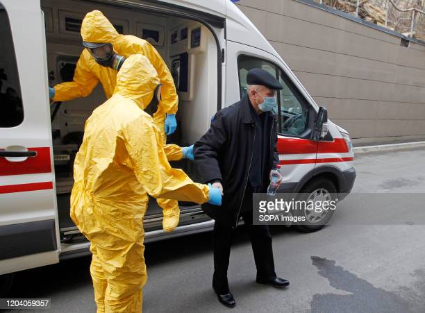Medics workers in protective clothes accompany a man acting to have coronavirus during the COVID19 corona virus response training exercise at the...
