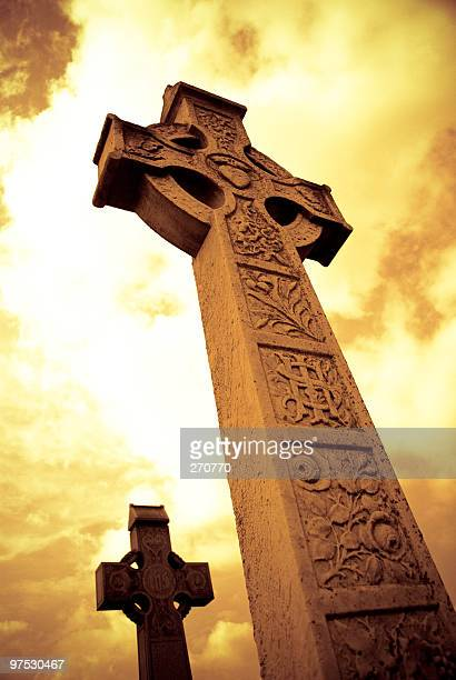 Medieval Celtic Cross with sunset colors in Irish cemetery