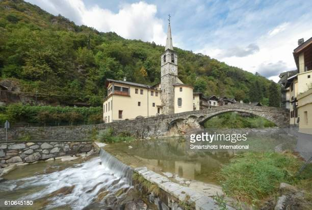 medieval church and bridge crossing river lys in fontainemore, gressoney, aosta valley, italy - apse stock photos and pictures