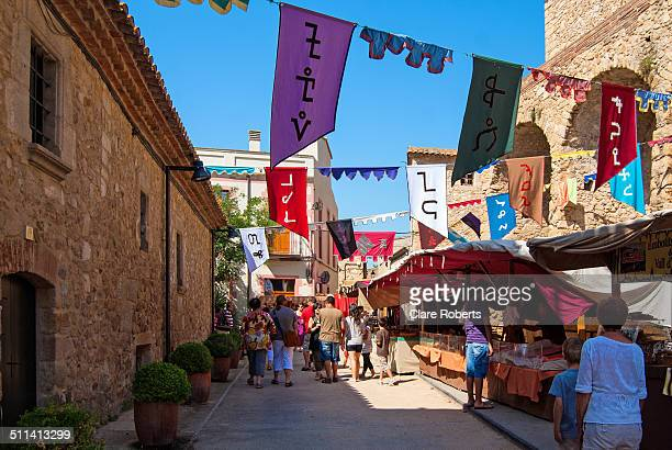 A medieval festival which takes place every year in the small Spanish town of Castell D'Aro Summer tourists stroll through the streets looking at the...