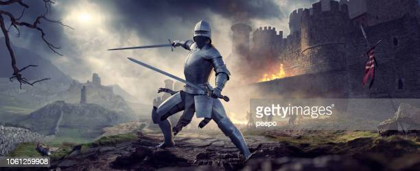 medieval knight in armour holding two swords near burning castle - castle stock pictures, royalty-free photos & images