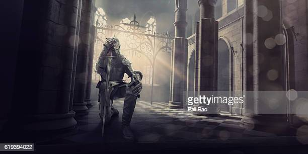 medieval knight in armour kneeling with sword inside castle - ritter stock-fotos und bilder